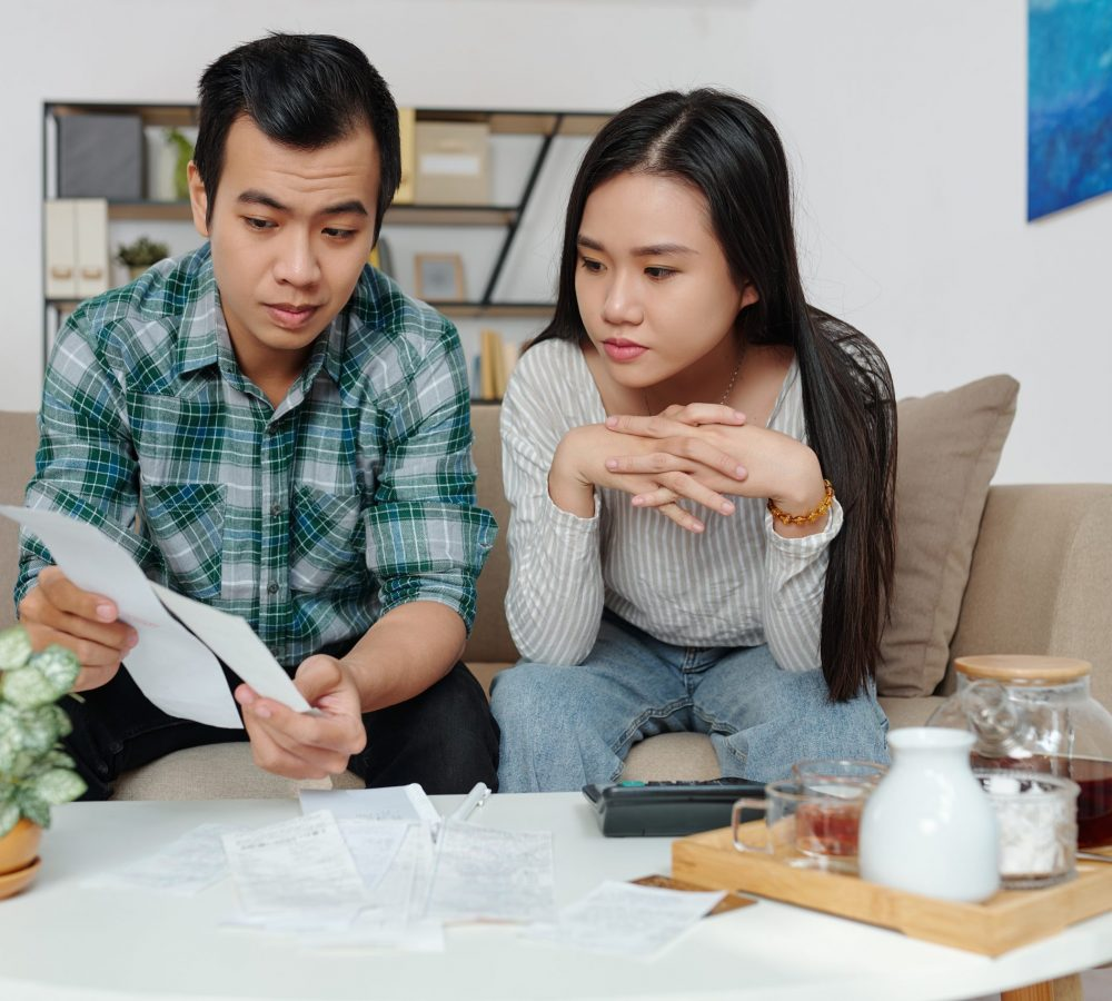 Vietnamese young man showing bills to girlfriend when they are discussing and managing personal expenses and utility bills